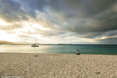 The girl is doing yoga on Whitehaven Beach at sunset, with an upcoming storm.